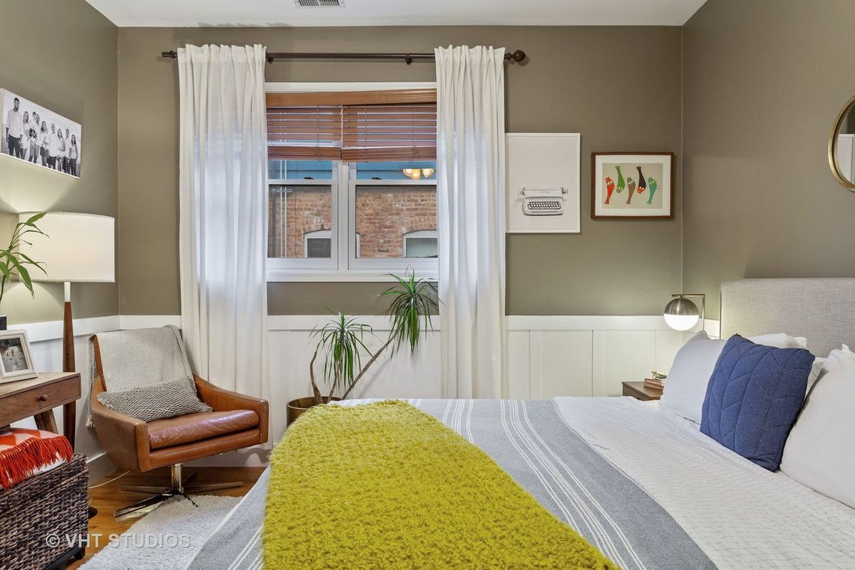 A second bedroom with a single window, wainscoting along the wall, and a leather swivel  chair.