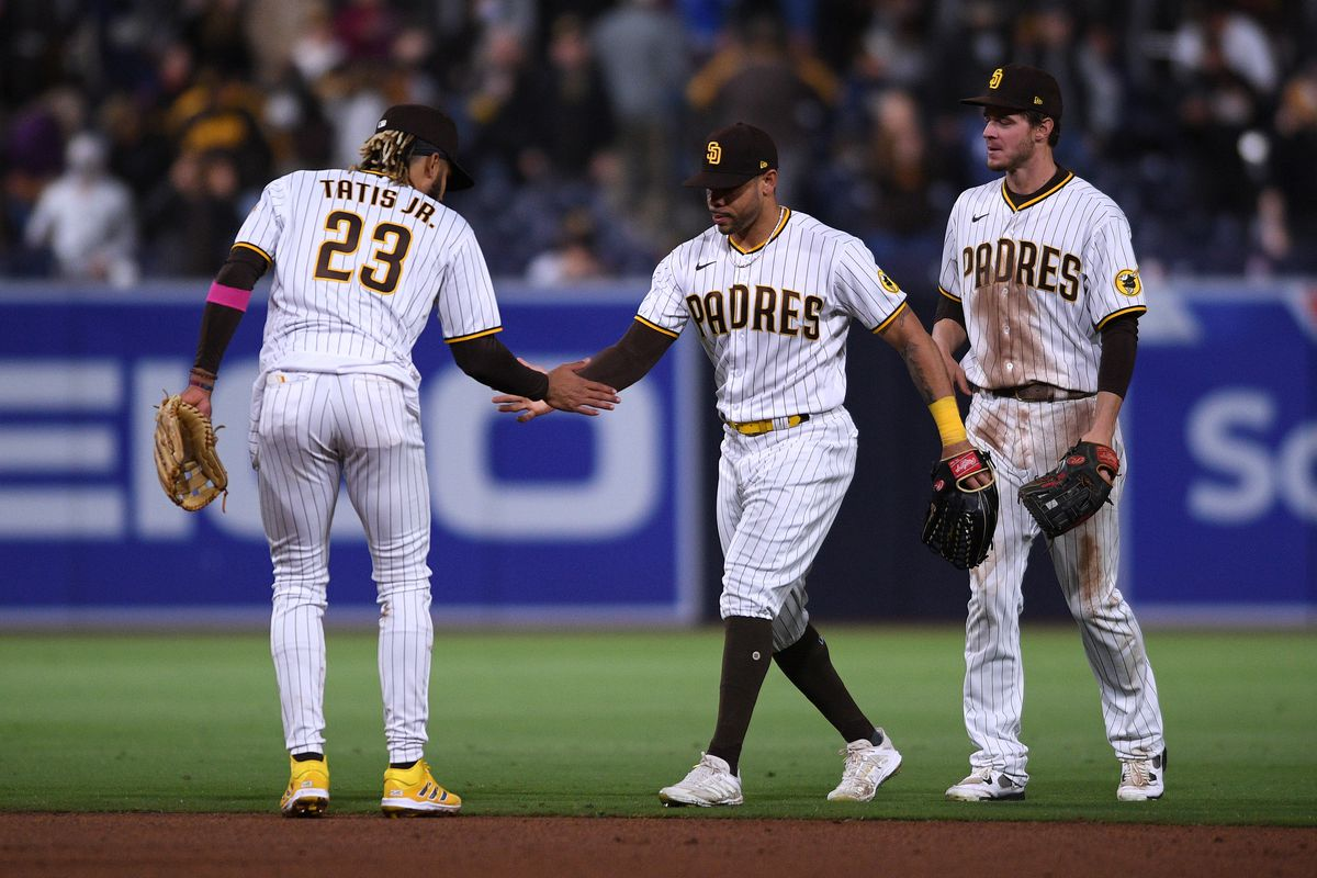 San Diego Padres shortstop Fernando Tatis Jr. and left fielder Tommy Pham celebrate on the field after defeating the Pittsburgh Pirates as right fielder Wil Myers looks on at Petco Park.