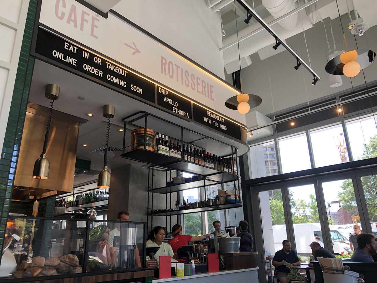 A low angle shows a counter with a coffee bar and overhanging shelves filled with wine, plus a rotisserie oven in the background