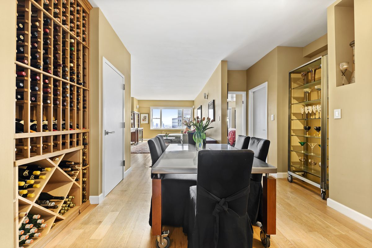 A living room with built-in wine storage, hardwood floors, and a dining table.