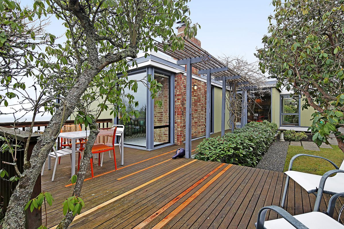 One corner of the house can be seen surrounded by a wooden deck and a courtyard.