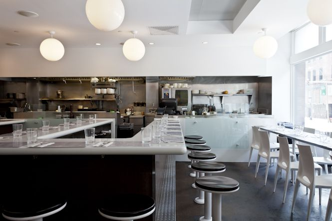 Interior view of a restaurant with white walls, light countertops, and sleek backless bar stools