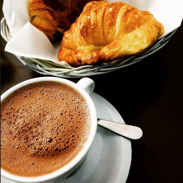 A cup of hot chocolate sits next to a basket with croissants.