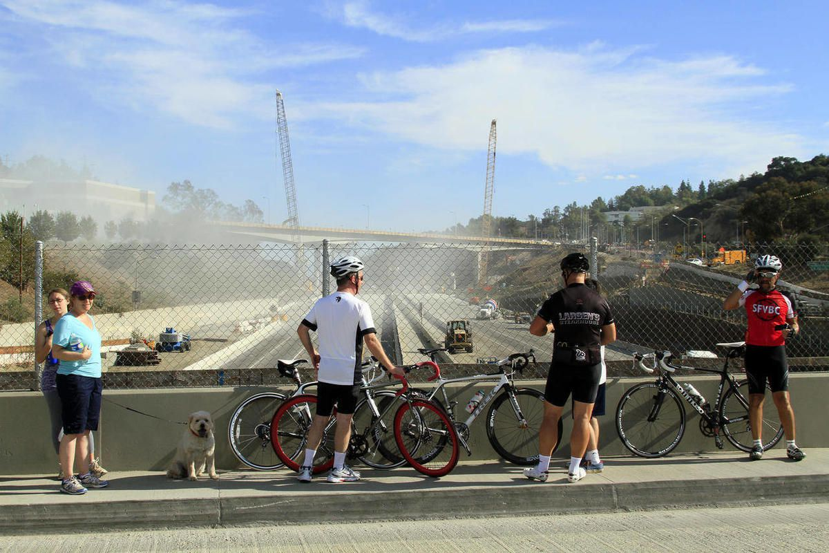 Morning walkers and bicyclists stop on Skirball Bridge to view and photograph heavy equipment busy in the demolition of part of the Mullholland Drive bridge over the 405 freeway early Sept. 29, 2012 in Los Angeles. Construction crews began work early Satu