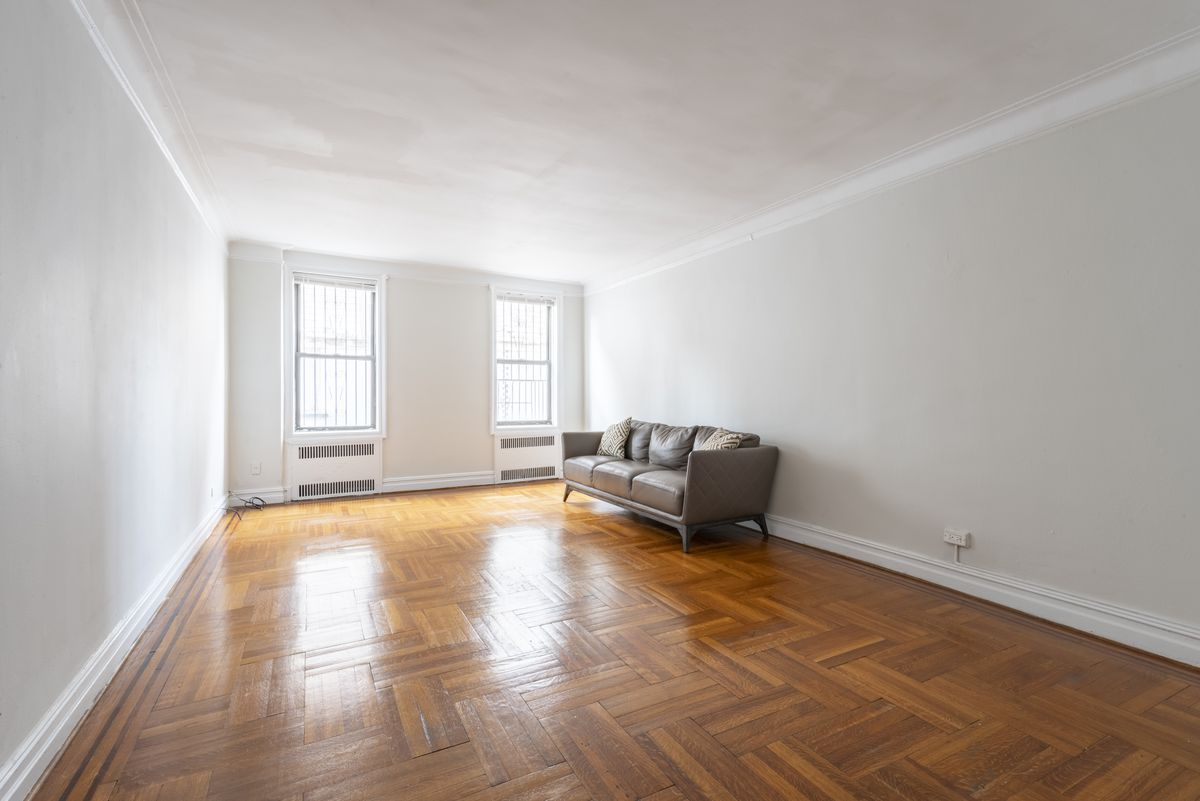 A living room with a couch, hardwood floors, and two windows.