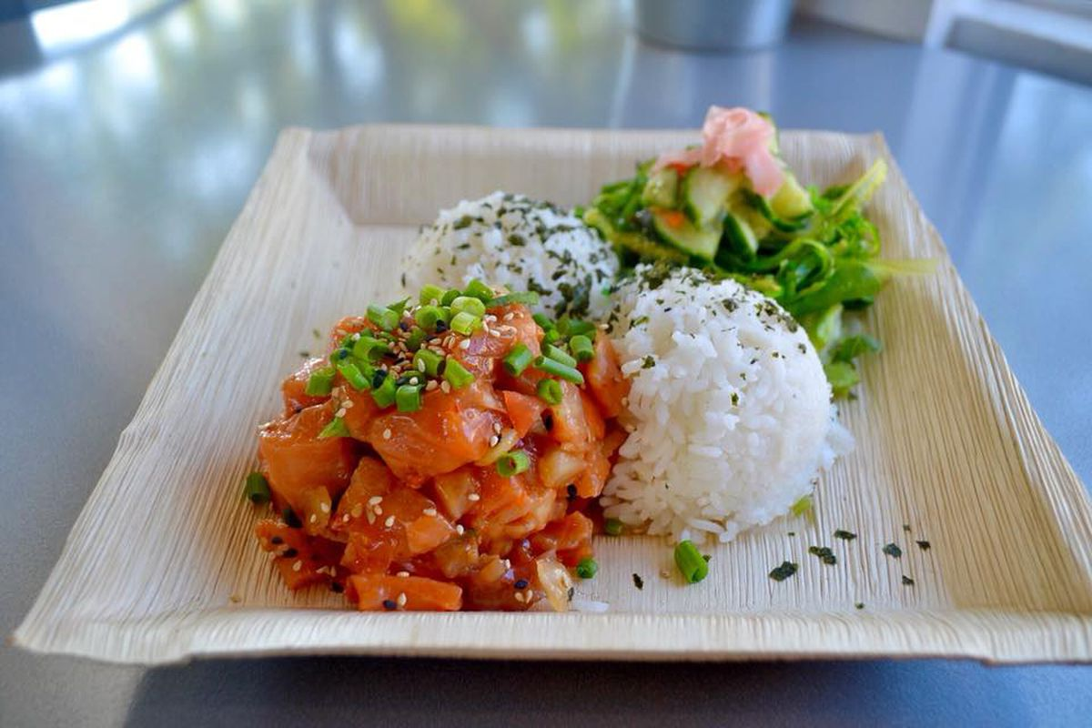 A pile of marinated poke next to a scoop of rice on a cardboard tray.