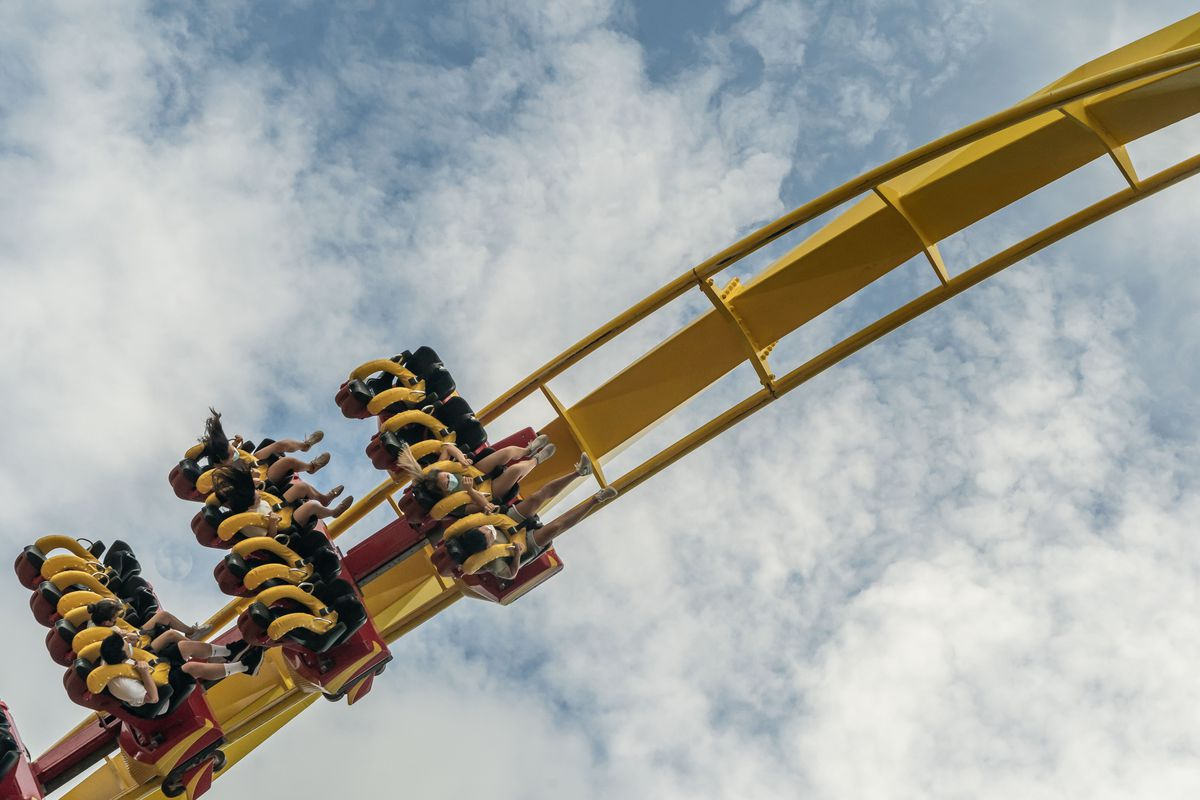 Visitors wearing protective masks ride on a roller coaster at Ocean Park during the parks reopening on September 18, 2020 in Hong Kong, China.
