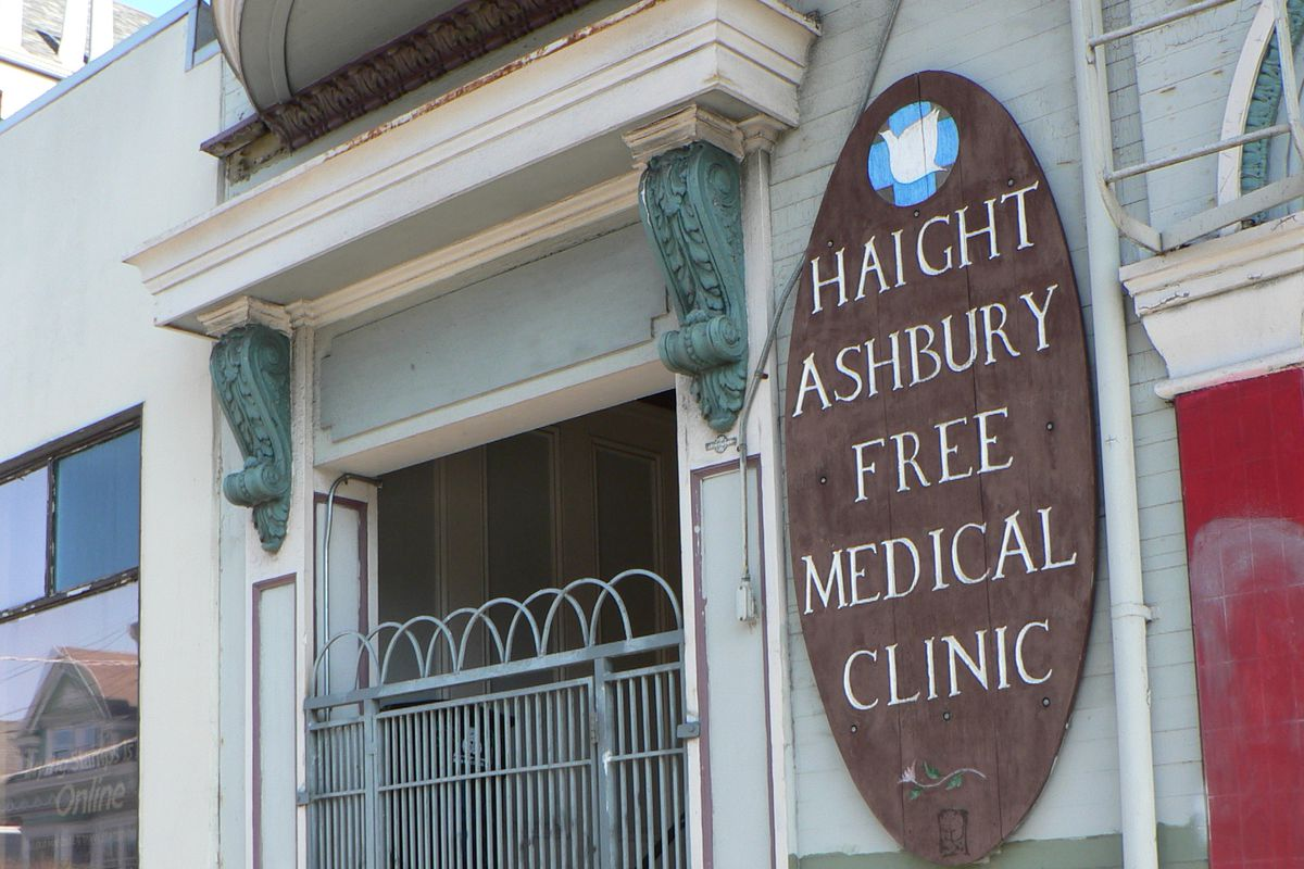 """A Victorian house with a large oval sign reading """"Haight-Ashbury free clinic."""""""