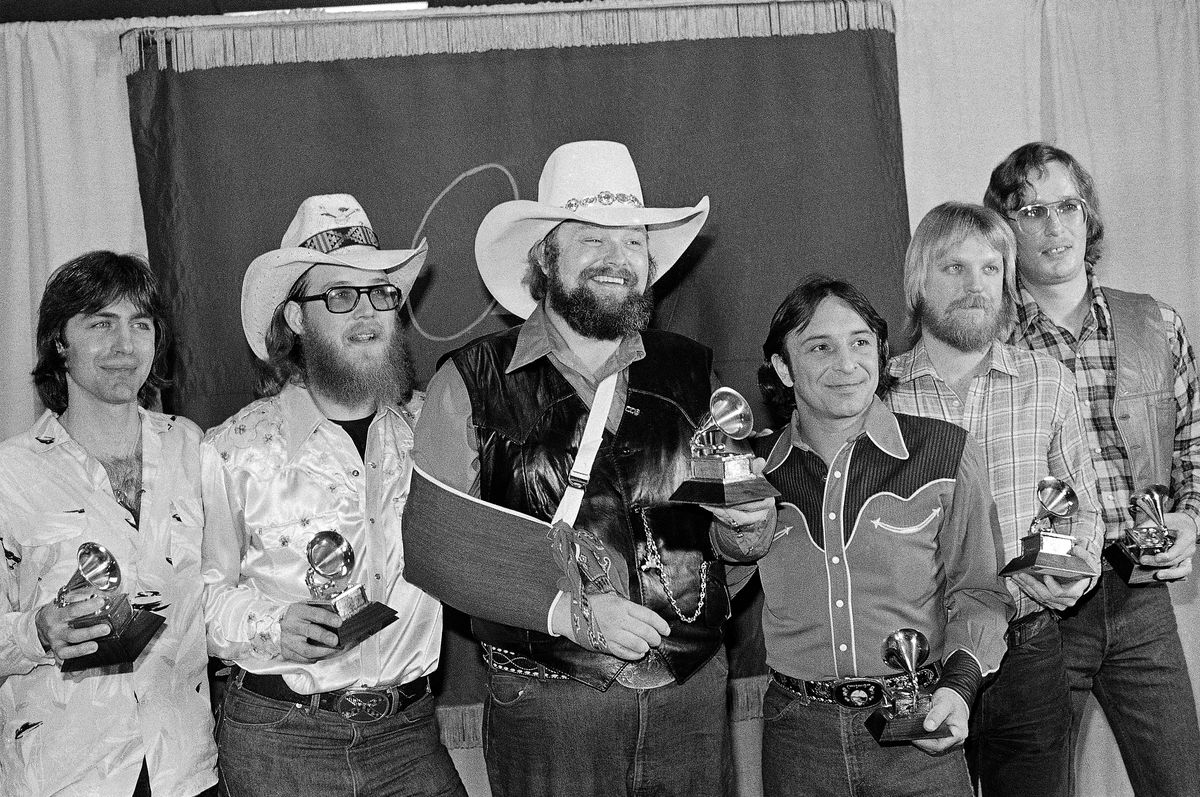 """Charlie Daniels (center) joins members of the Charlie Daniels Band with their Grammy Awards in Los Angeles in 1980, as best country vocal performance by a group for their hit """"The Devil Went Down To Georgia."""""""