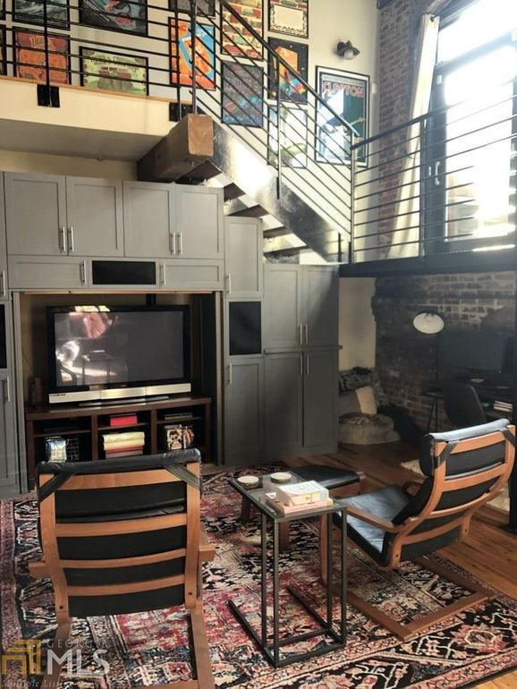 A staircase with a TV beneath it and chairs.