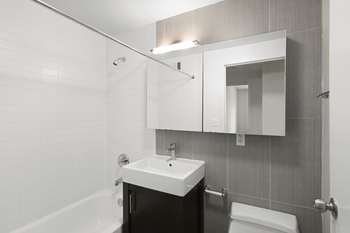 A bathroom with white and light brown tiles.