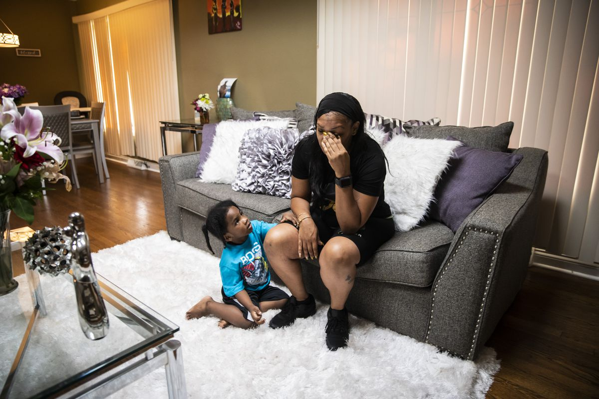 Carmela Richardson, 39, sits on the couch with one of her six remaining children, 4-year-old Caiden Richardson, as she prepares to write the obituary for her oldest son in the family's West Pullman neighborhood home, Wednesday evening, July 14, 2021. Carmela Richardson's 19-year-old son Myron Richardson's body was found shot in the head in the trunk of a burning car July 6 not far from their home on the Far South Side.