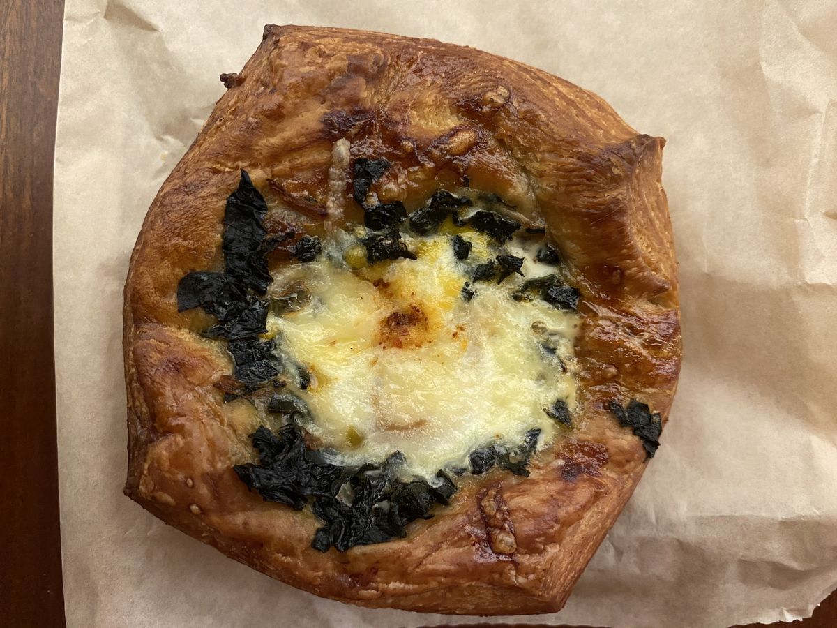 An egg tart with kale and comte sits on a brown paper wrapper