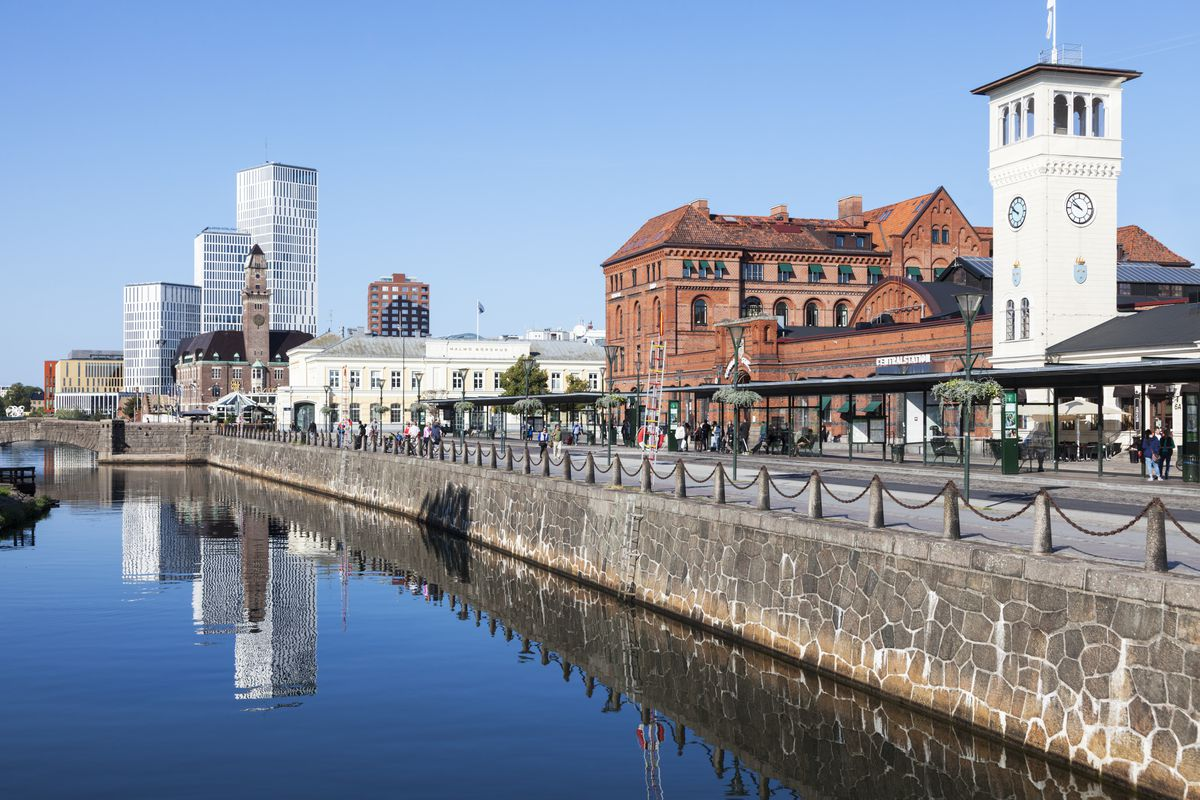 A riverwalk with a stone wall leading down to a canal, and old and new buildings mixed in the background
