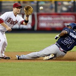 Atlanta Braves' Michael Bourn (24) steals second base as Arizona Diamondbacks' Aaron Hill makes the catch during the first inning of a baseball game, Friday, April 20, 2012, in Phoenix.