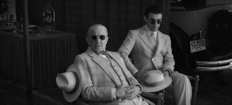 Two men in suits and shades circa the early 1930s sit together.