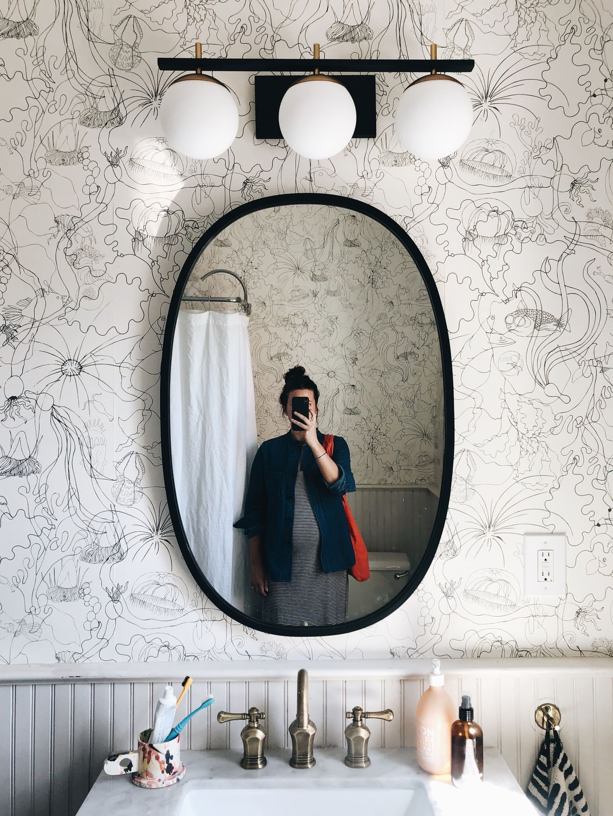 A woman stands in front of an oval bathroom mirror with her cell phone covering her face. A wall sconce hangs above the mirror with three round bulbs against a simple white wallpaper with black etchings.