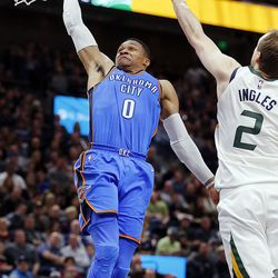 Oklahoma City Thunder guard Russell Westbrook dunks the ball with Utah Jazz forward Joe Ingles at right during NBA basketball in Salt Lake City on Saturday, Dec. 23, 2017.