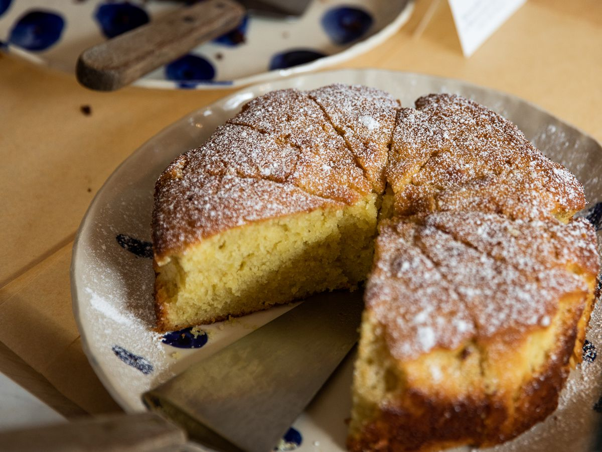 Olive oil cake with one slice removed sits in a display case next to a slice of chocolate cake at Ochre Bakery.