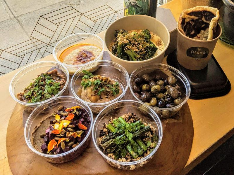 Eight takeout containers featuring dips, olives, and salads