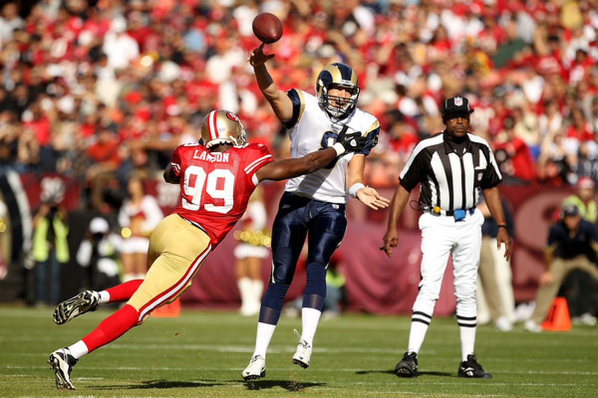 Sam Bradford #8 of the St. Louis Rams throws the ball as he is hit by Manny Lawson #99 of the San Francisco 49ers at Candlestick Park on November 14 2010 in San Francisco California.  (Photo by Ezra Shaw/Getty Images)