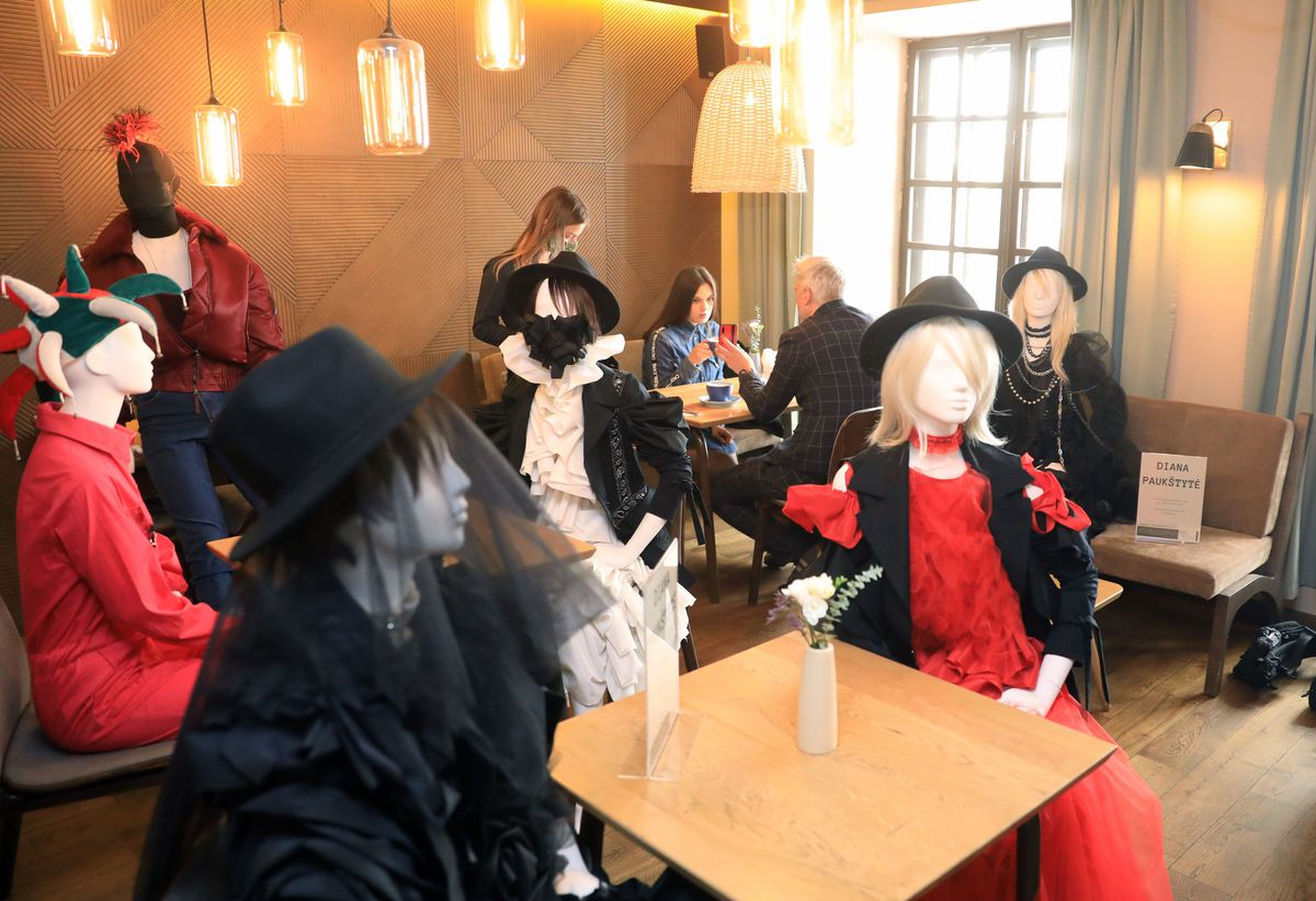 Mannequins dressed in evening gowns, hats, and festive attire placed all over a restaurant interior.