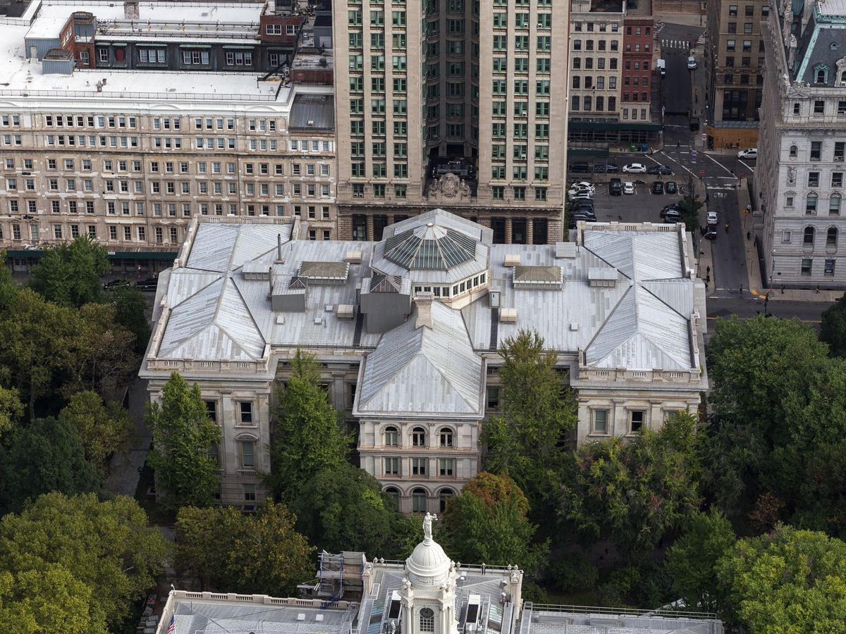 An aerial view of Tweed Courthouse in New York City. The building is large with a light grey roof. There are trees surrounding the building. Other city buildings are in the background.