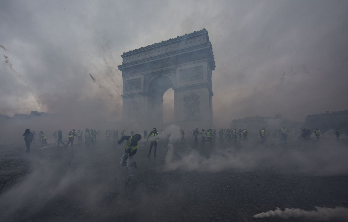 Teargas surrounds protesters when they collide with the riot police during a demonstration of