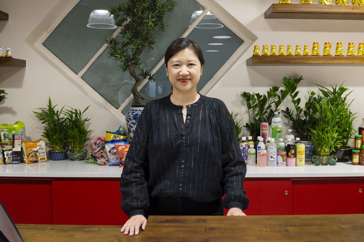 Pearl River Mart Foods proprietor Joanne Kwong stands behind the counter wearing a black long-sleeved shirt