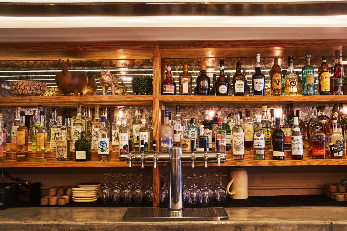 Shelves behind a bar are stocked with bottles of mezcal, tequila, and liquor, along with copitas and glassware for service