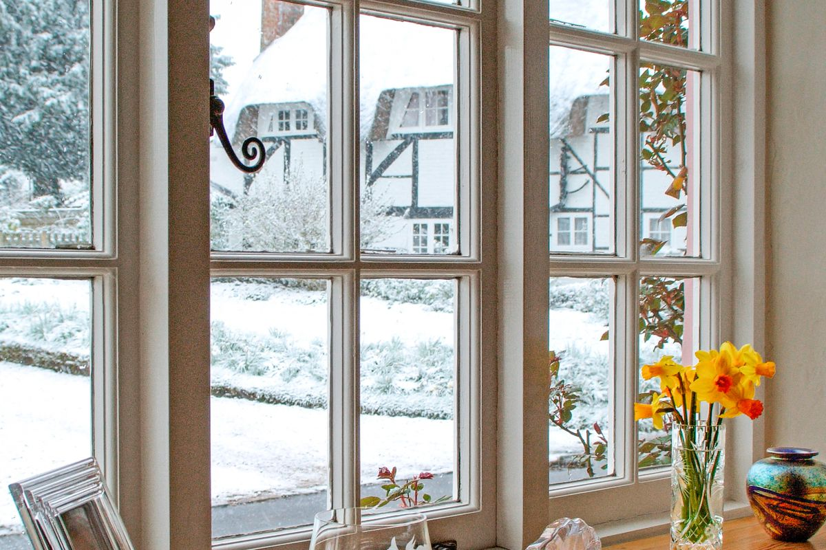 White framed windows with view of snow outside.