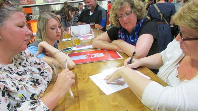 Teachers from IPS School 79 work on their answers at Education Trivia Night at Sun King Brewery sponsored by Chalkbeat and WFYI Public Media.