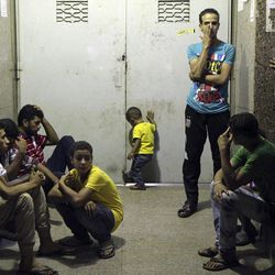 In this Friday Sept. 14, 2012 photo, family members of Ismail Rashad, 36, wait for his body to be released outside the door to the Zenhoum morgue in Cairo, Egypt. His family and doctors at a Cairo hospital said Rashad  died yesterday from wounds from rubber bullets in clashes Friday that brought the first Egyptian to be killed in Tahrir Square protests since Islamist President Mohammed Morsi was elected and took office this summer.