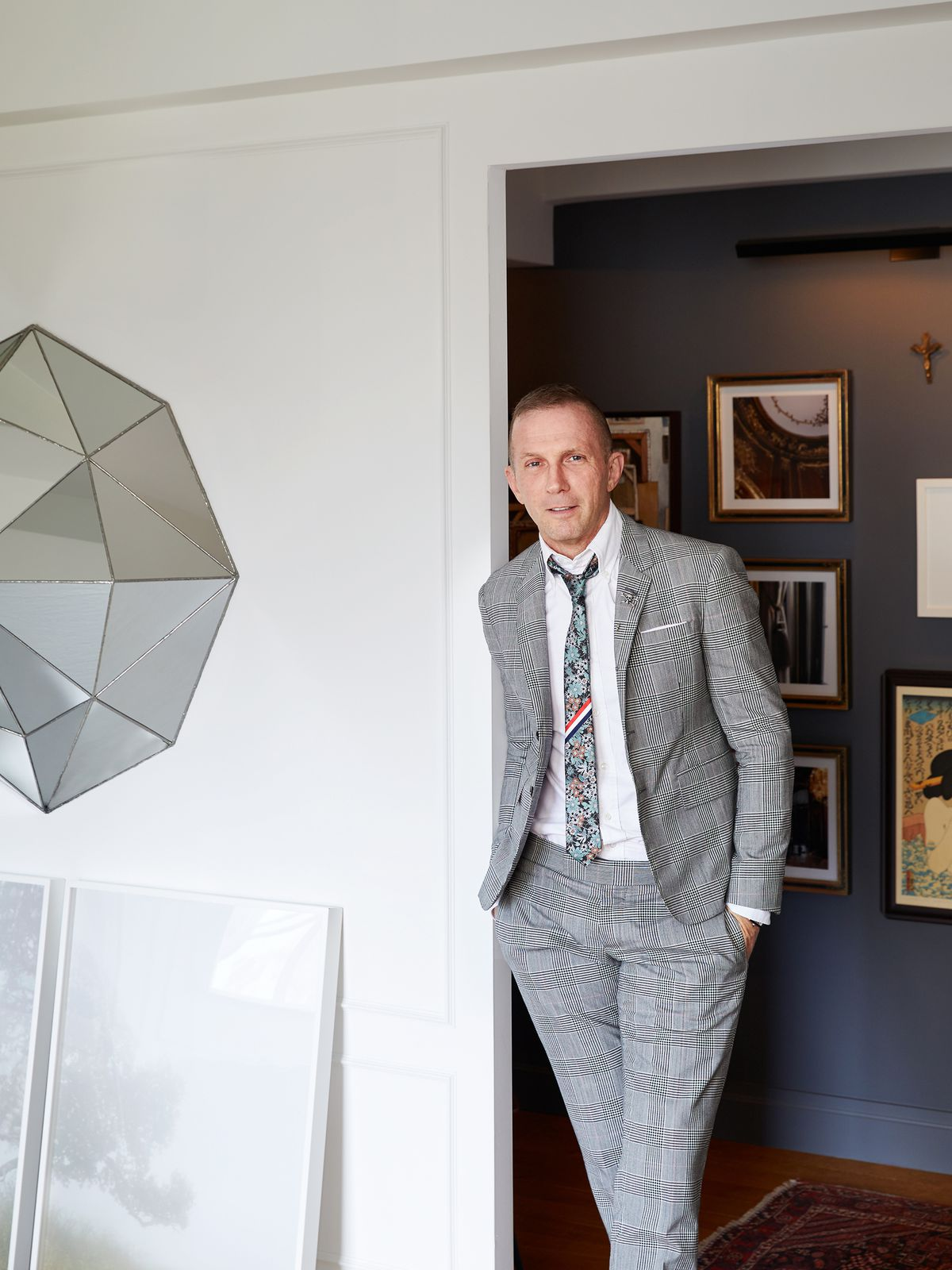 Designer Tim Campbell stands in a doorway in his apartment. He wears a plaid suit.