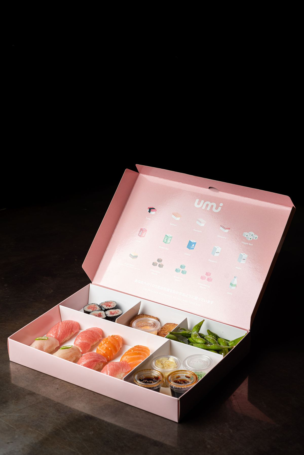 A pink sushi box filled with fish against a black background.