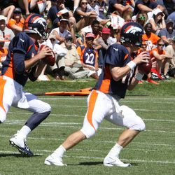 Quarterbacks Brock Osweiler (left) and Peyton Manning (right) move together during passing drills