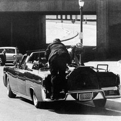 FILE - In this Nov. 22, 1963 file photo, first lady Jacqueline Kennedy leans over President John F. Kennedy as Secret Service agent Clinton Hill rides on the back of their car after the president was shot in Dallas.  The Secret Service has been tarnished by a prostitution scandal that erupted April 13, 2012 in Colombia involving 12 Secret Service agents, officers and supervisors and 12 more enlisted military personnel ahead of President Barack Obama's visit there for the Summit of the Americas.
