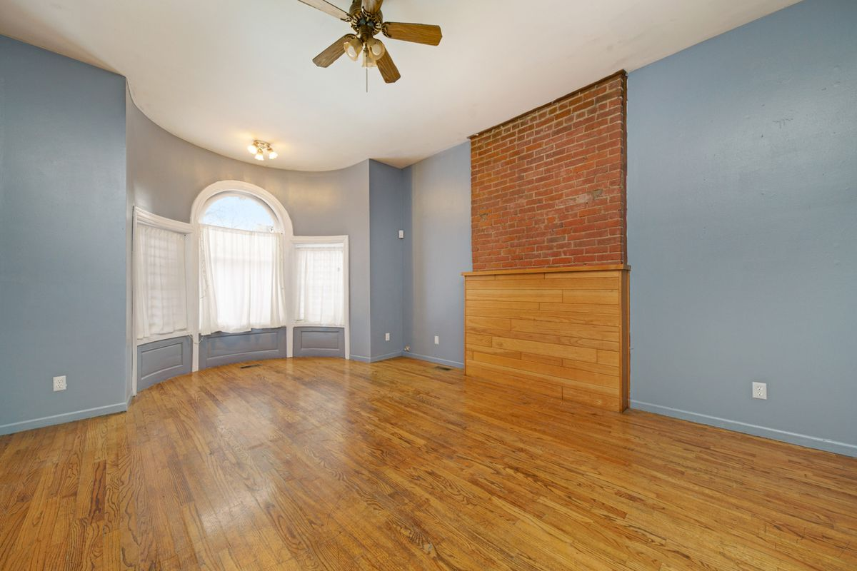A big living room with wood floors and light blue walls. There's a bay window and a brick chimney with wood covering the fireplace.