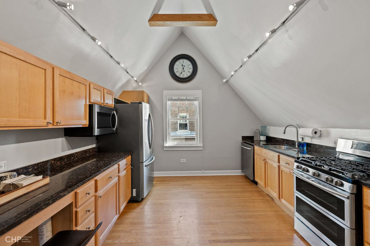 The kitchen features new appliances, black countertops, and blonde wood cabinets.