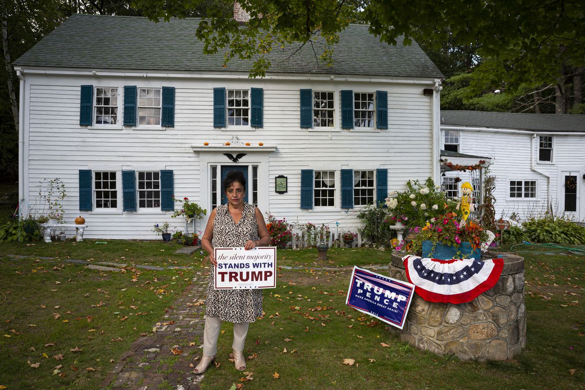 """Patty Femino holds a sign, with President Donald Trump's autograph, that reads """"the silent majority stands with Trump"""" outside her home in Wolfeboro, N.H., on Sunday, Sept. 15, 2019."""