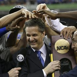 Kentucky head coach John Calipari, center, celebrates with his team after the NCAA Final Four tournament college basketball championship game against Kansas Monday, April 2, 2012, in New Orleans. Kentucky won 67-59.