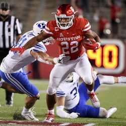Houston running back Kyle Porter (22) escapes a tackle from BYU defensive lineman Hirkley Latu, left, during the first half of an NCAA college football game on Friday, October 16, 2020 in Houston.