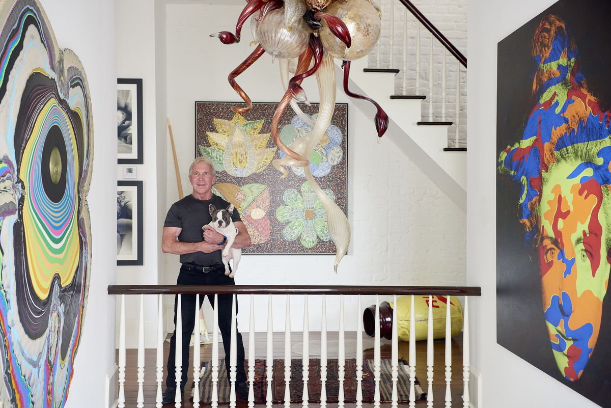 Arthur Roger holds his black-and-white French bulldog, Bumble, on the winding staircase of his home. Colorful art surrounds him.