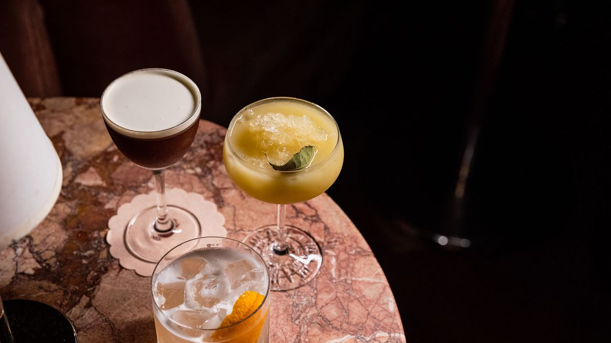 three cocktails on a circular pink marble table