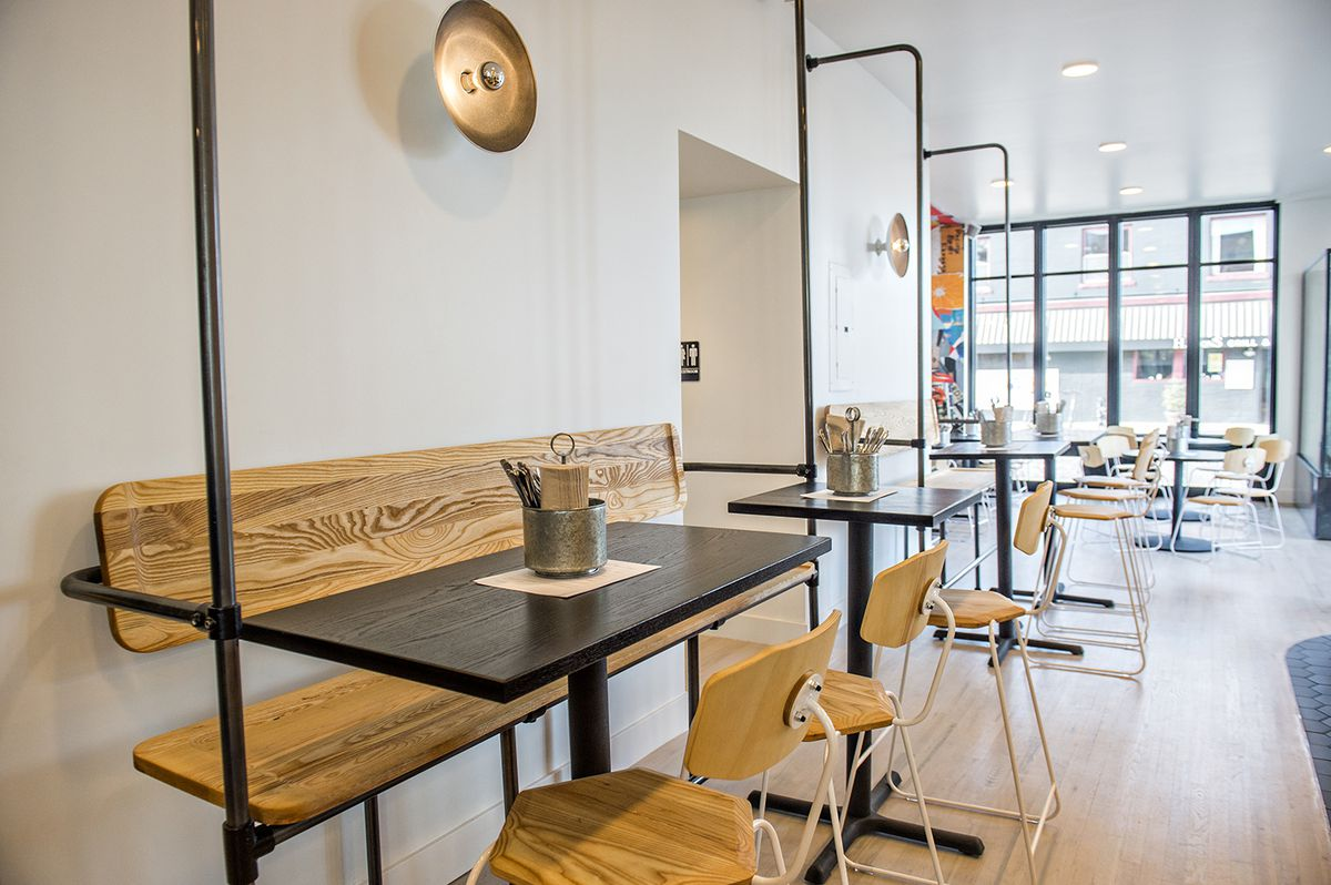 A photo of the dining room at Chook focused on a black table with a wooden bench.