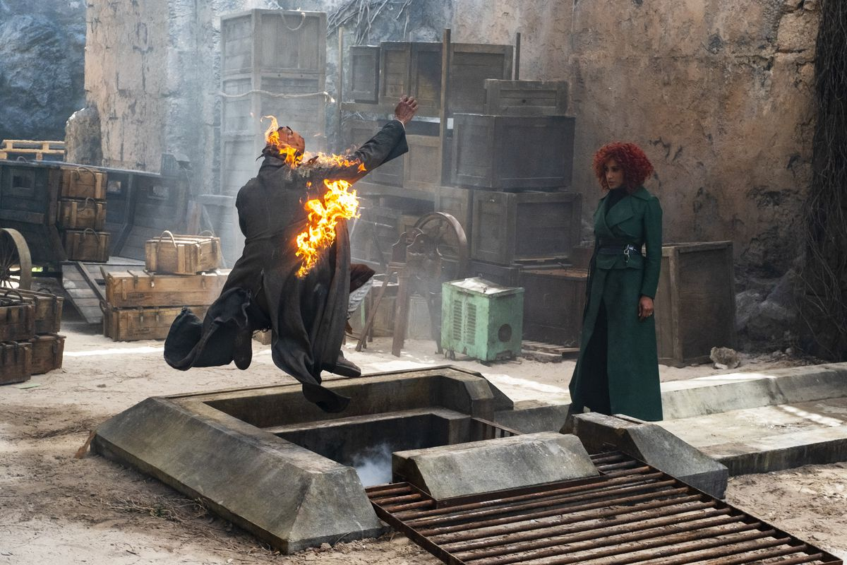 Lara Rossi as Lady Sybil Ramkin stands in front of a broad grate with someone on fire in The Watch