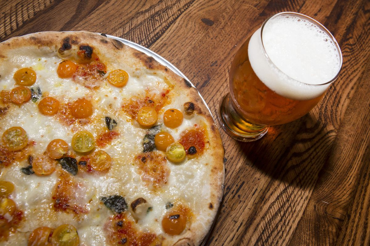 A pizza on a pan with yellow tomatoes next to a pilsner beer in a glass.