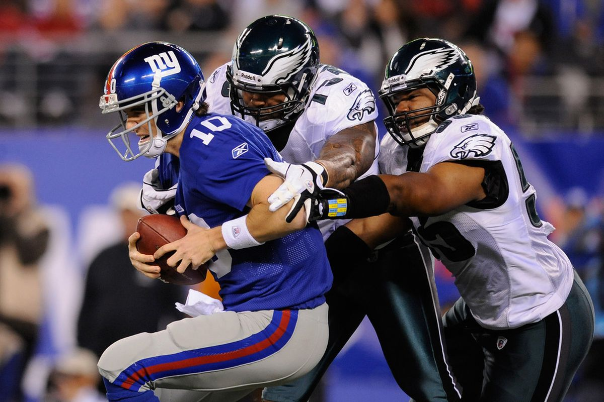 Eli Manning of the New York Giants is sacked by Juqua Parker (75) and Darryl Tapp (55) of the Philadelphia Eagles at MetLife Stadium on November 20, 2011 in East Rutherford, New Jersey.  (Photo by Patrick McDermott/Getty Images)