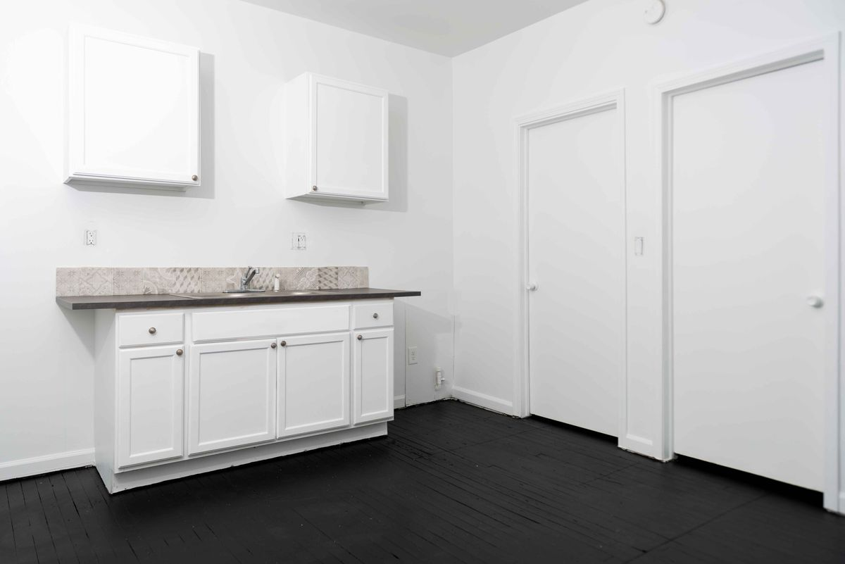 A kitchen with white cabinets and no appliances.