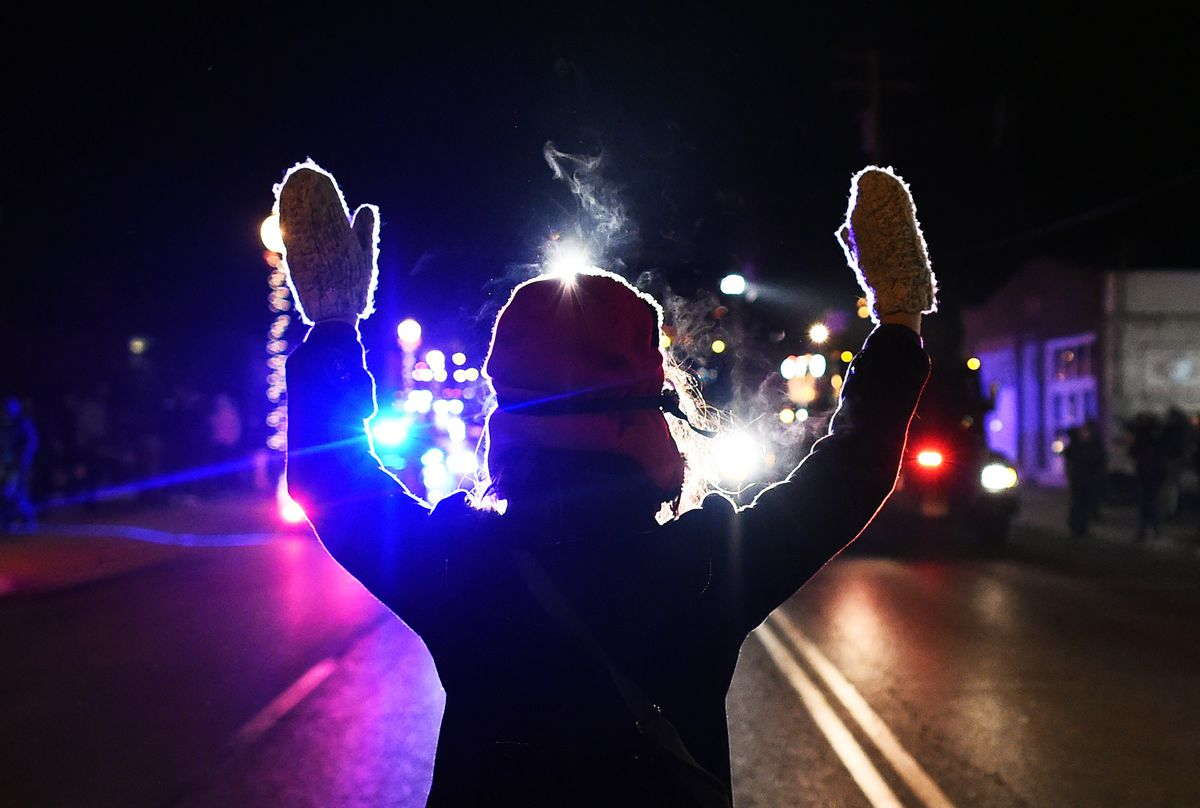 """A protester does the """"hands up, don't shoot"""" motion."""